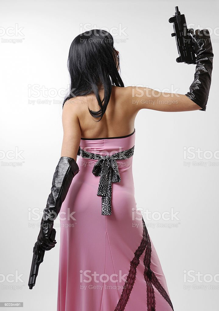 Woman in long dress with guns, rear view stock photo