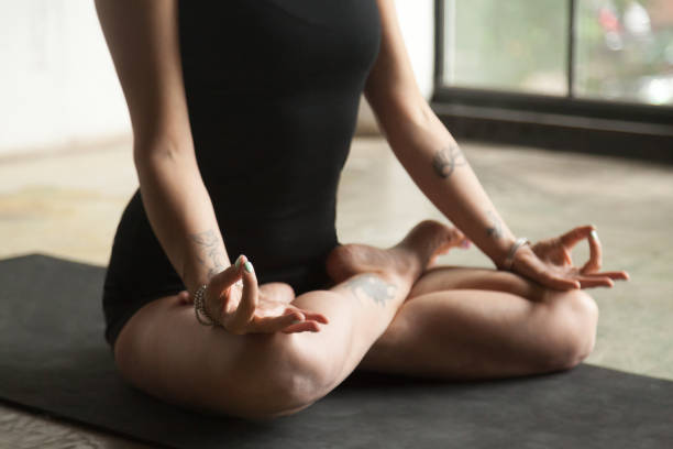 frau in lotus pose closeup, mat studio-hintergrund - buddhist tattoos stock-fotos und bilder