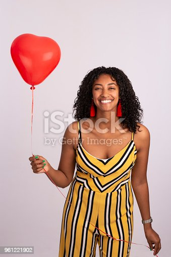 Studio shot portrait of a smiling young beautiful woman looking at the camera, holding a red heart-shaped balloon. The woman wearing yellow black white stripes overall, red earrings, isolated over white.