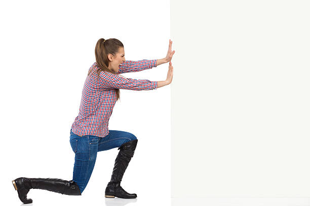 Woman In Lumberjack Shirt Pushing Wall stock photo