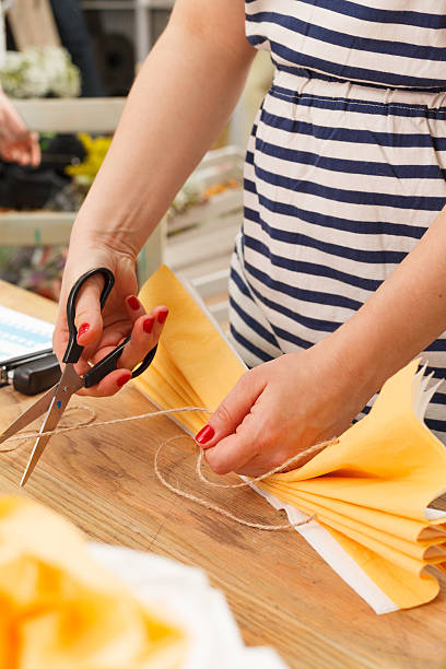 woman in making a yellow paper flower stock photo