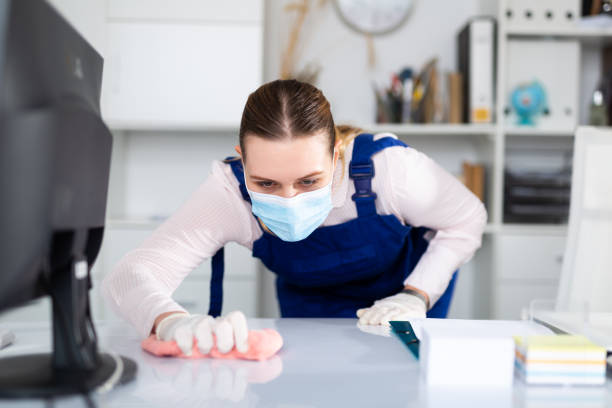 Woman in mask, gloves and overall disinfecting office stock photo