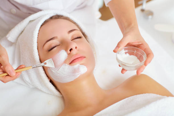 Woman in mask on face in spa beauty salon stock photo