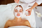 Woman in mask on face in spa beauty salon.