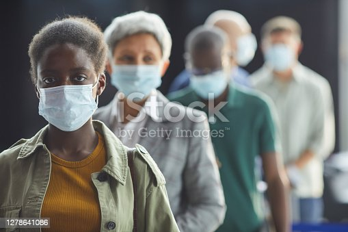Portrait of young African woman in protective mask looking at camera while standing in a queue