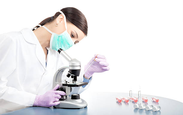 Woman in mask using pipette and microscope. stock photo