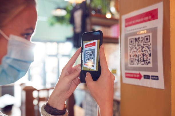 Woman In Mask With Mobile Phone Checking Into Venue Scanning QR Code During Health Pandemic stock photo