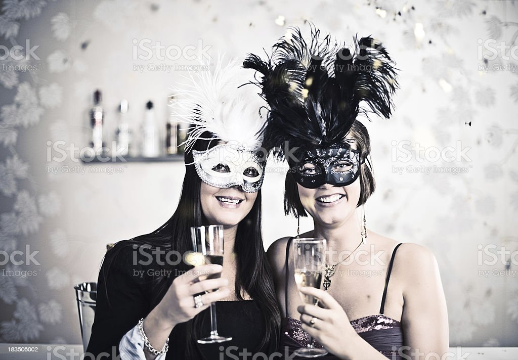 Woman in masks and drinking champagne royalty-free stock photo