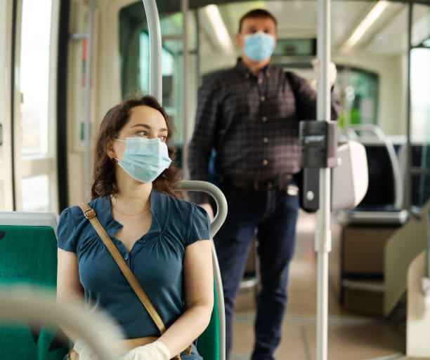 Woman in medical mask sitting in streetcar stock photo