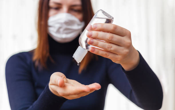 Woman in medical protective mask applying an antiseptic gel for hands disinfection and protection against flu virus. Coronavirus quarantine. stock photo