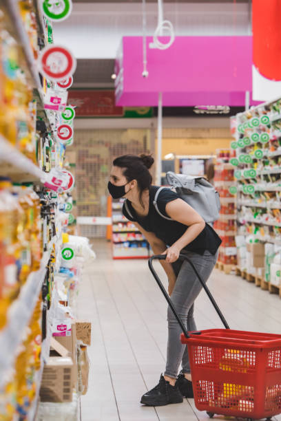 woman in medicine mask do groceries shopping stock photo
