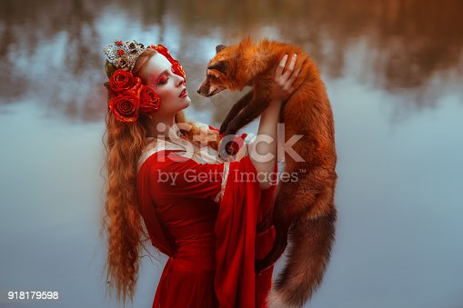 861629426 istock photo Woman in medieval clothes with a fox 918179598
