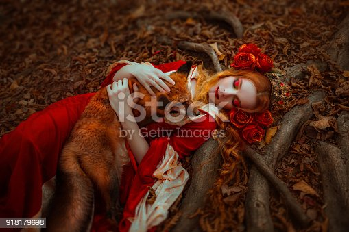 861629426 istock photo Woman in medieval clothes with a fox 918179698