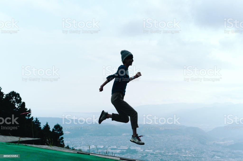 Woman in mid-air jump above mountain ledge stock photo
