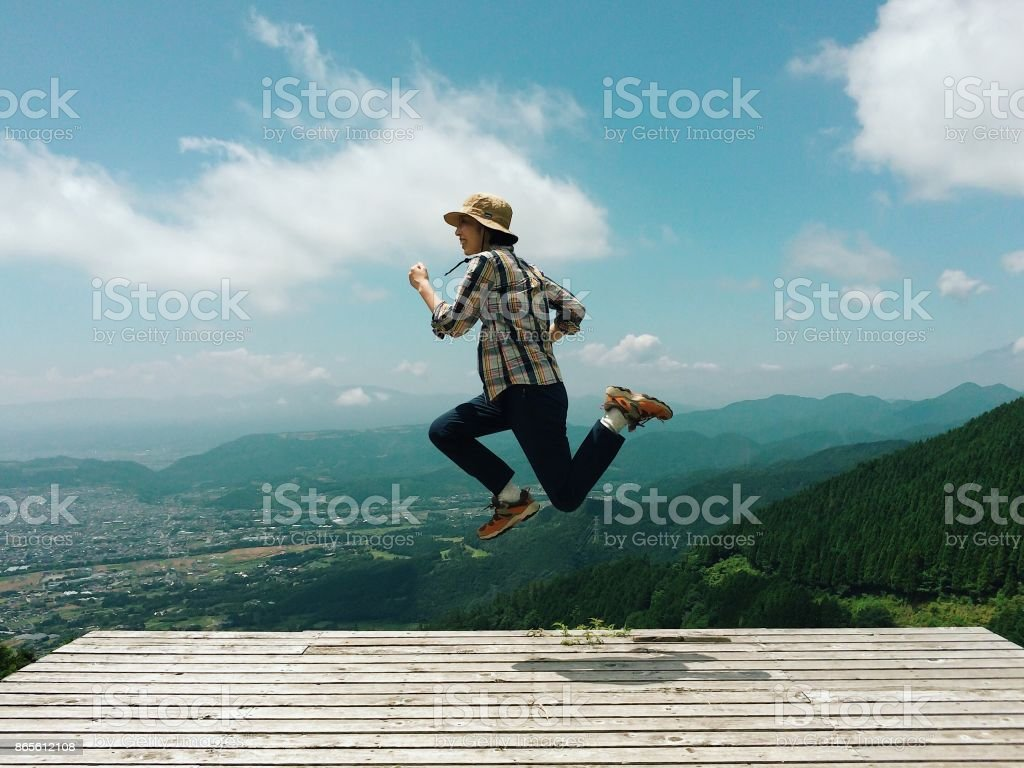 Woman in mid-air jump above mountain ridge stock photo