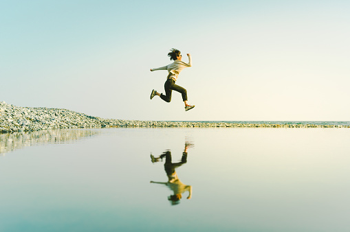 486439381 istock photo Woman in mid-air jump above water Reflected in Big Puddle. 1193303510