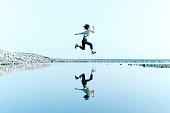 上記の大きな水たまりに映った水空中ジャンプの女性