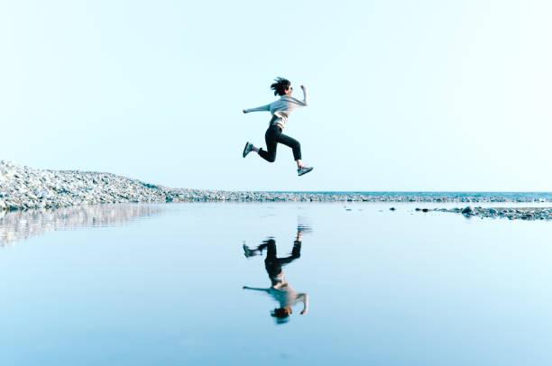 上記の大きな水たまりに映った水空中ジャンプの女性 ストックフォト