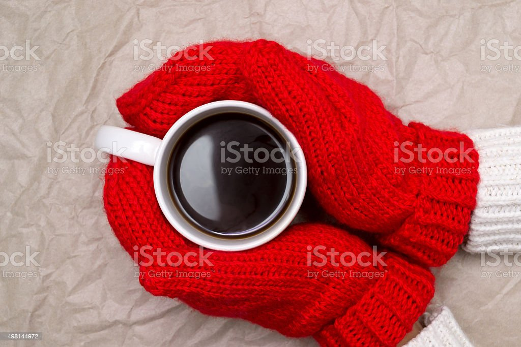 Woman in mittens and cup of coffee stock photo