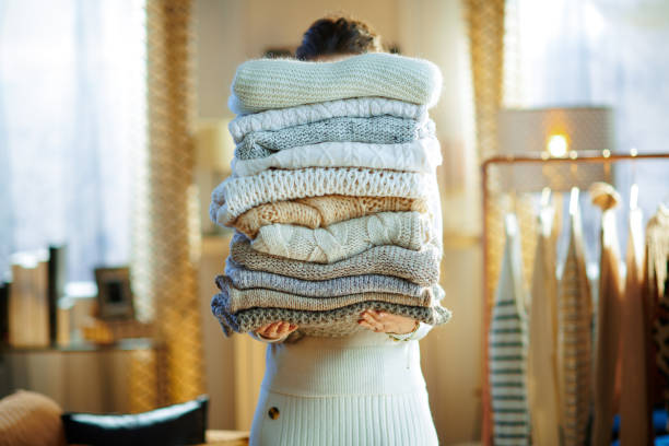 woman in modern house in sunny winter day holding huge sweaters stock photo