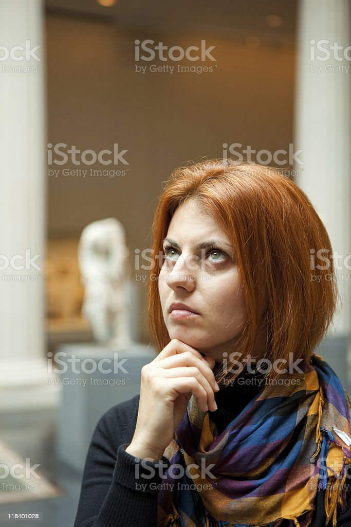 Woman in museum looking at fine art statue royalty-free stock photo