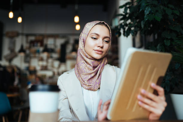 a woman in muslim clothes and a scarf works in a cafe - скромная одежда стоковые фото и изображения