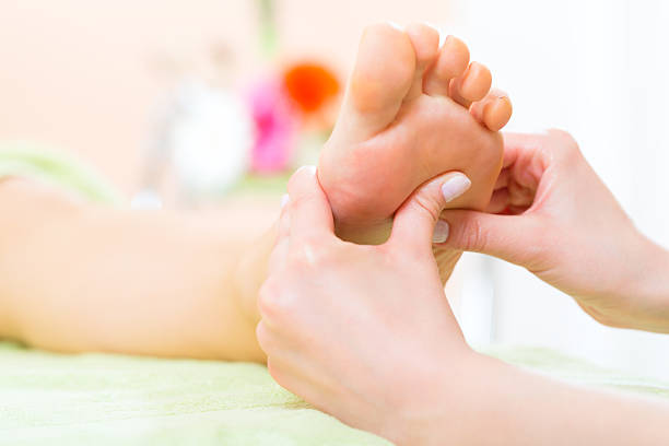 Woman in nail salon receiving foot massage Woman in a nail salon receiving a pedicure by a beautician, she is getting a foot massage foot massage stock pictures, royalty-free photos & images