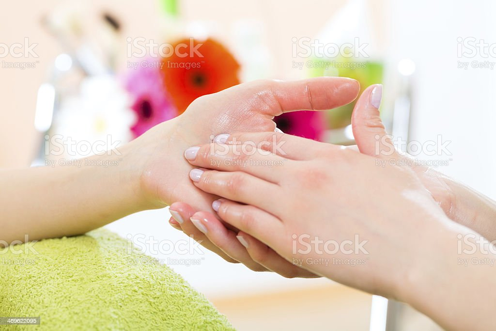 Woman in nail salon receiving hand massage stock photo