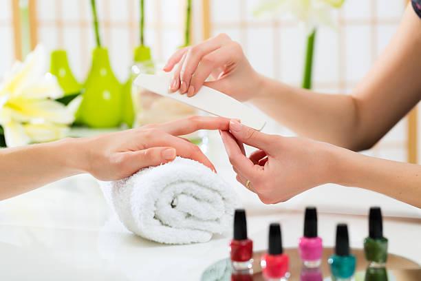 mulher em salão de manicure receber manicure - manicure - fotografias e filmes do acervo