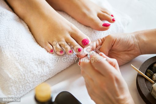 istock Woman in nail salon receiving pedicure by beautician 545984710