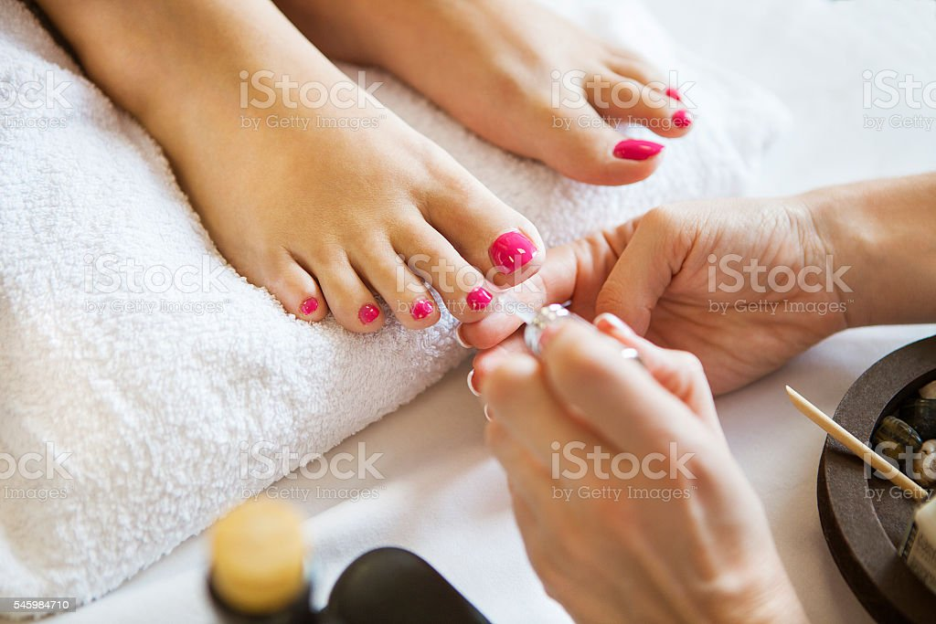 Woman in nail salon receiving pedicure by beautician stock photo