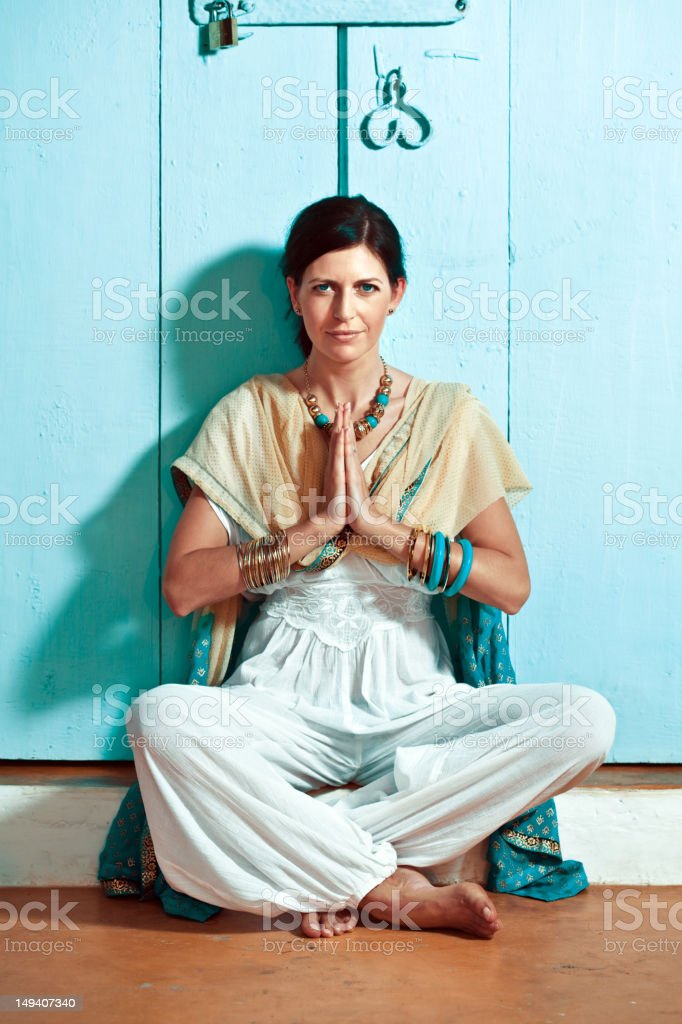 Woman in namaste pose Beautiful woman on the exotic vacation, sitting cross-legged with a traditional namaste greeting, looking at camera and smiling. 30-34 Years Stock Photo