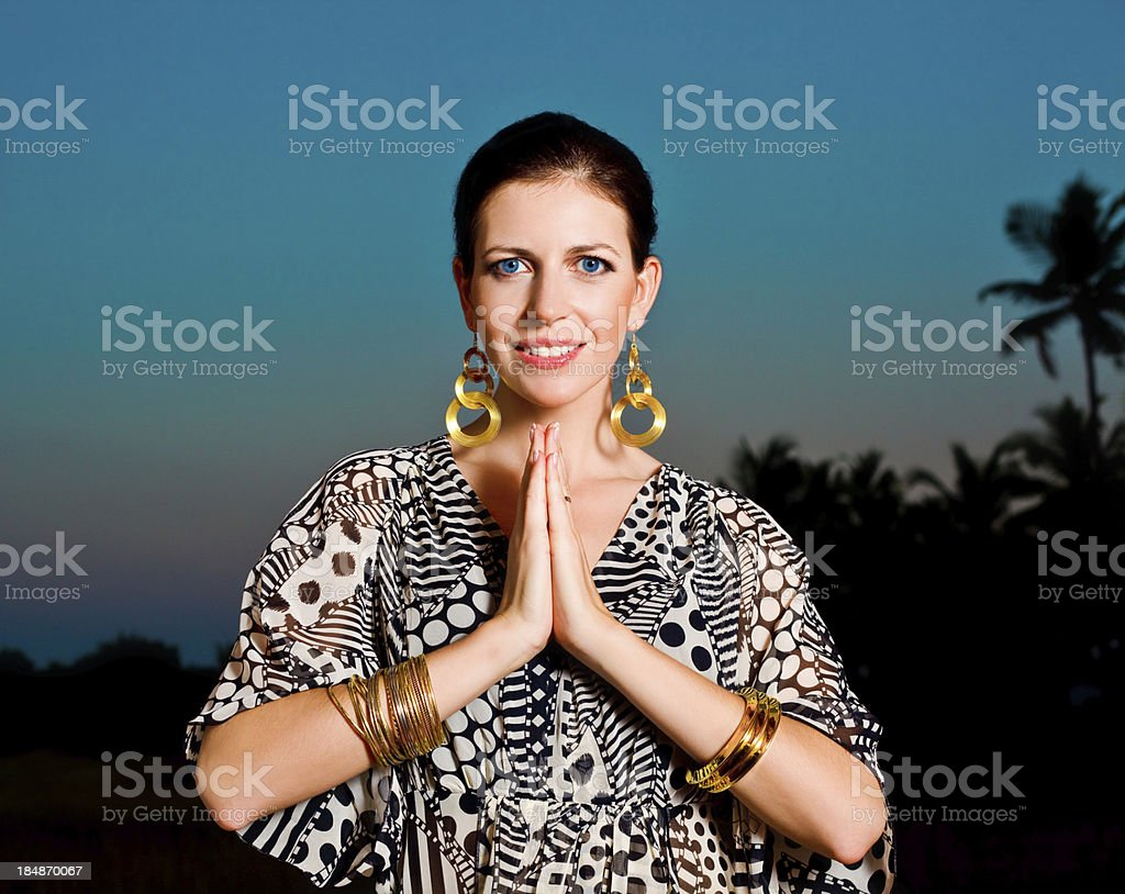 Woman in namaste pose Beautiful woman on the exotic vacation with a traditional namaste greeting, looking at camera and smiling. 30-34 Years Stock Photo