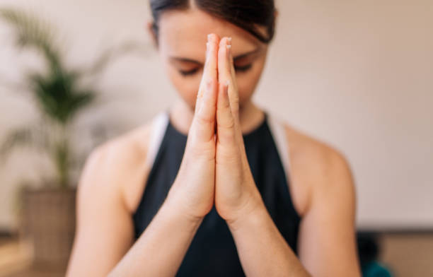Woman in namaste yoga pose meditating Close up of woman hands joined. Female meditating with her hands joined indoors. Namaste yoga pose, meditating, breathing and relaxing. prayer pose yoga stock pictures, royalty-free photos & images