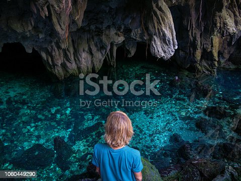 Woman in natural lake inside cave. Colorful reflection, turquoise transparent water, summer adventures. Tourist destination, Kei Islands, Moluccas, Indonesia.