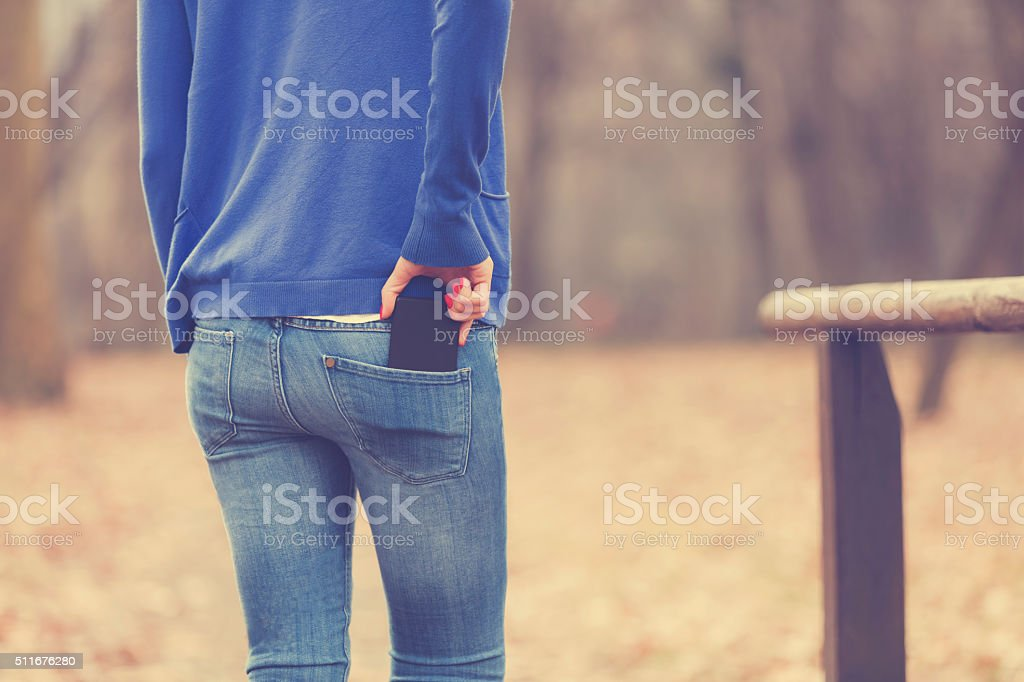 Woman in nature holding cellphone. stock photo