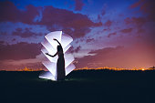 Woman silhouette in nature in front of light painting.