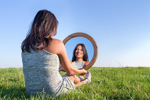 Woman in nature viewing her mirror image stock photo