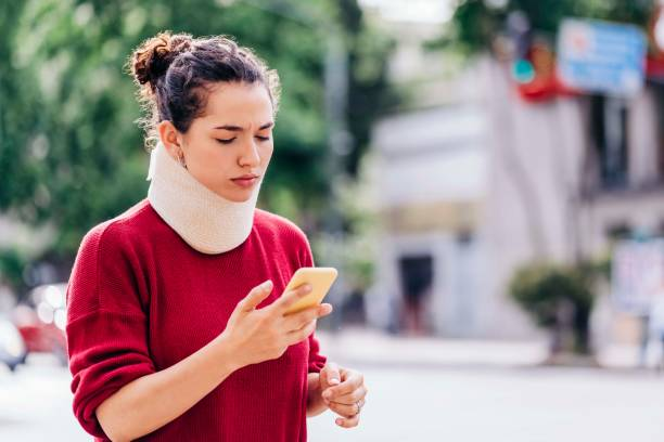 Woman in neck brace using mobile phone on street stock photo