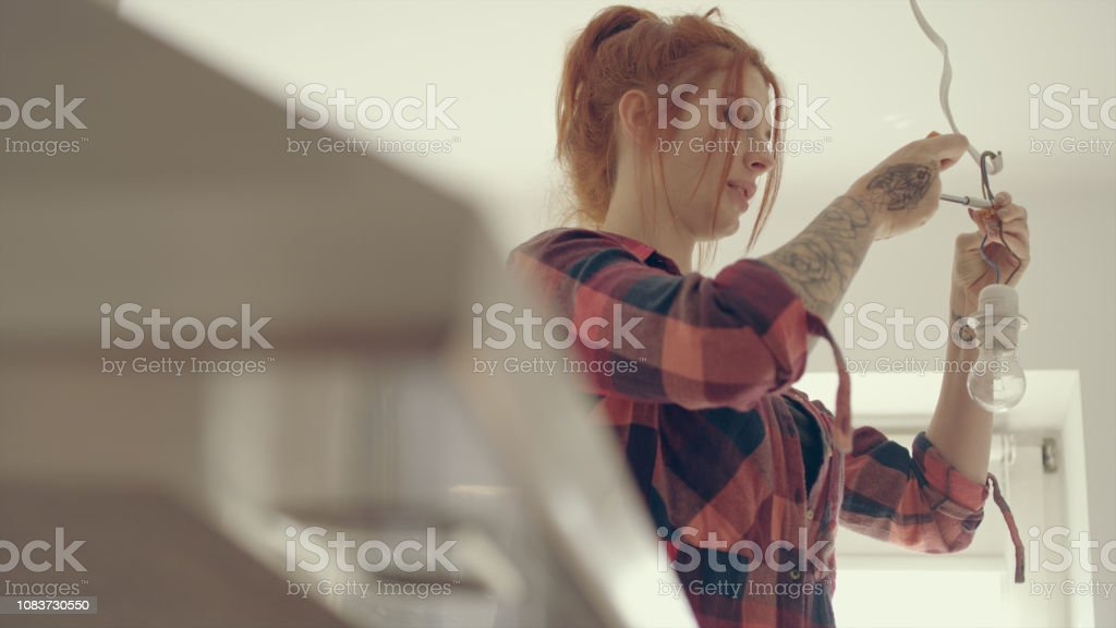 Woman in new home changing light bulb stock photo