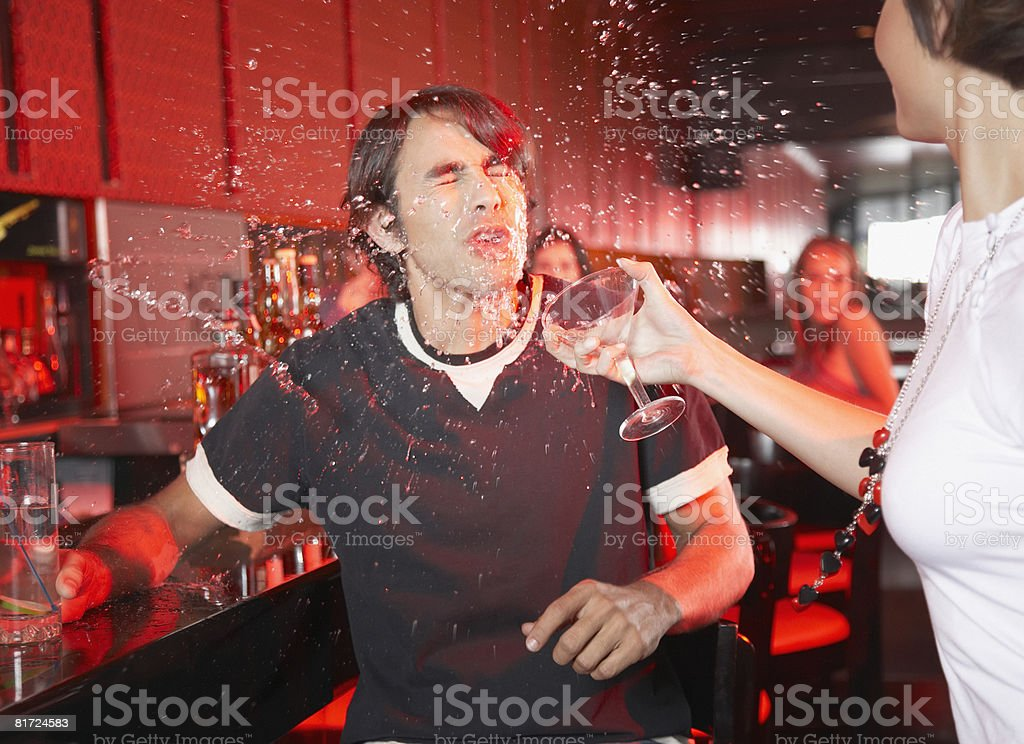 Woman in nightclub throwing beverage in man's face stock photo