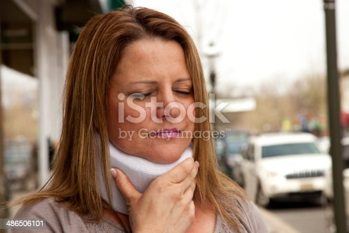 Attractive middle aged woman with long light brown hair facing camera outdoors on street in daylight wearing and clutching an orthopedic neck brace with one hand on front of brace, eyes closed in obvious discomfort. Image shot with Canon 5D Mark2 , 100 ISO, 24-115mm lens