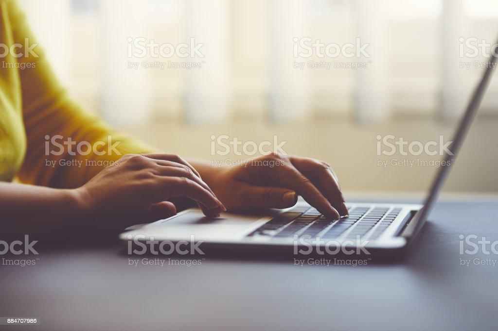 Frau im Büro hinter Tisch auf laptop – Foto