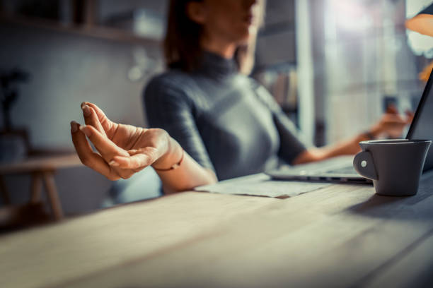 woman in office meditating - meditation stock pictures, royalty-free photos & images