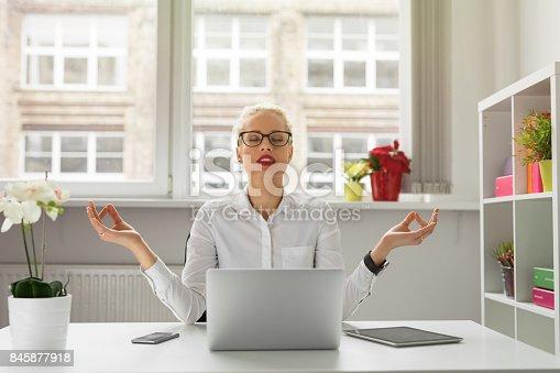 istock Woman in office meditating 845877918