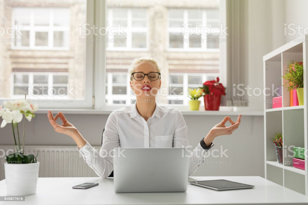 Woman in office meditating stock photo