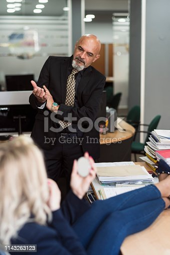 1130731761istockphoto Woman in office puts makeup on her lips and is surprised by boss 1143263123
