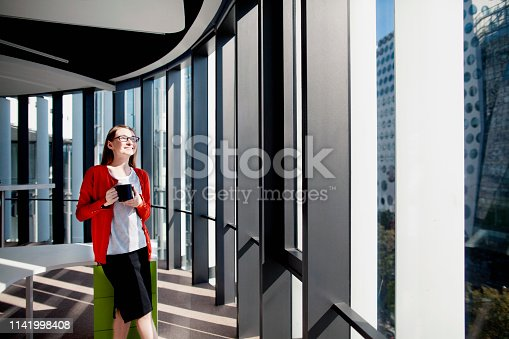 Woman in office smiling in sunshine in window drinking coffee