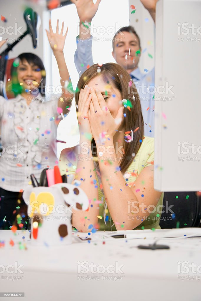 Woman in office with hands on face during celebration surprise stock photo