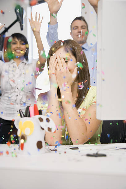 woman in office with hands on face during celebration surprise - geburtstagsgratulation stock-fotos und bilder